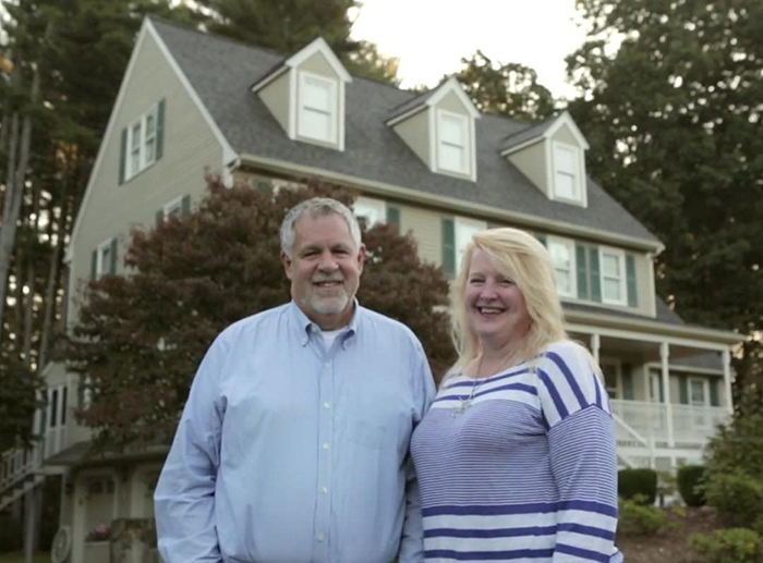 smiling couple in front of their house